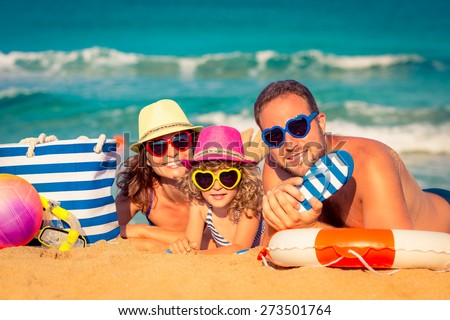 Happy family playing at the beach. Summer vacation concept - stock photo