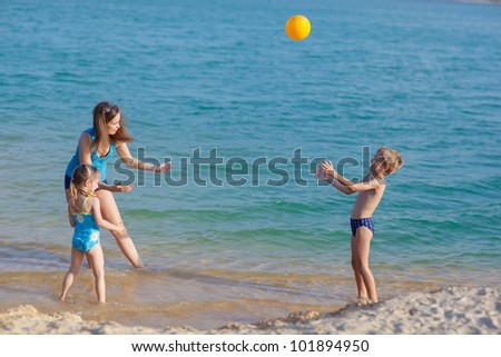 Happy family playing ball at the beach - stock photo