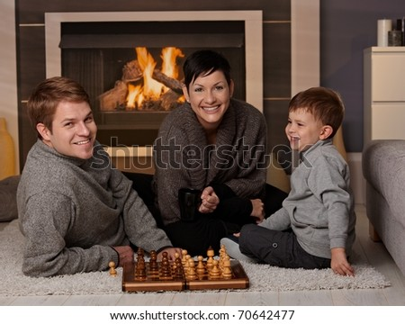 Happy family playing chess at home in a cold winter day, looking at camera, smiling.?