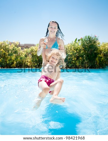 Happy family playing in blue water of swimming pool on a tropical resort at the sea. Summer vacations - stock photo