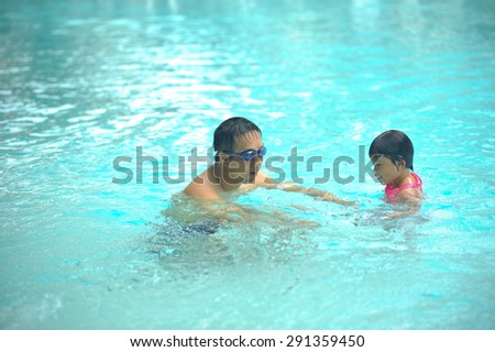 Happy family playing in swimming pool - stock photo
