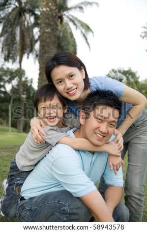 Happy family playing in the garden - stock photo