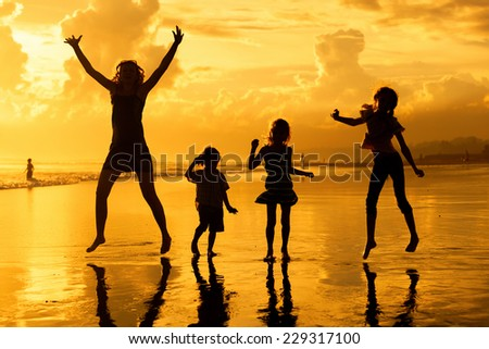 Happy family playing on the beach at the dawn time - stock photo