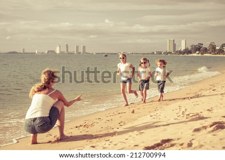 Happy family playing on the beach at the day time. - stock photo