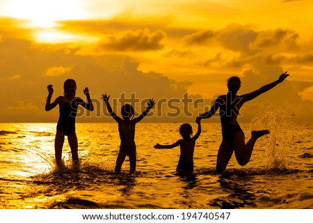 Happy family playing on the beach at the sunrise time