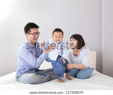 happy family playing on white bed in the bedroom at home, asian people - stock photo