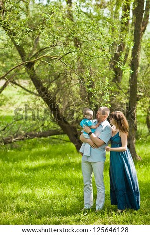 Happy family playing together in a picnic outdoors - stock photo
