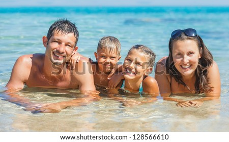 Happy family playing together in the transparent sea - stock photo