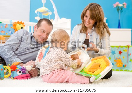 Happy family playing together: mother, father and 1 year old baby girl sitting on floor at children's room, smiling. Toys are officially property released. - stock photo