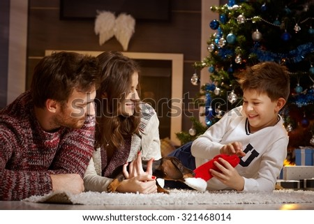 Happy family playing together with little dachshund puppy at christmas time. - stock photo