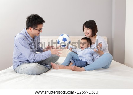 happy family playing toy soccer on white bed in the bedroom at home, asian people - stock photo