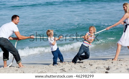 Happy family playing tug of war at the beach - stock photo