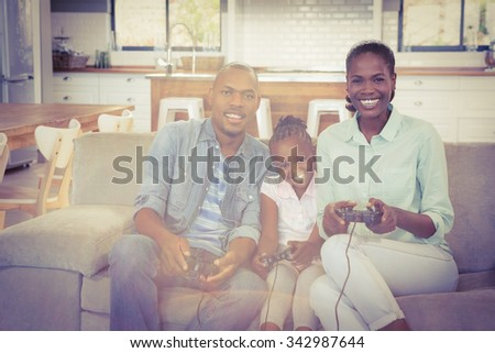 Happy family playing video games in living room - stock photo