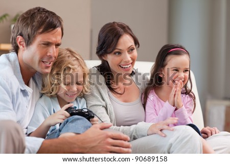 Happy family playing video games together in a living room