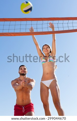 Happy family playing volleyball and having fun at the sea shore  - stock photo