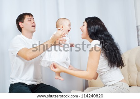 Happy family playing with a baby  at home - stock photo