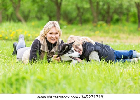 Happy family playing with a husky puppy. - stock photo
