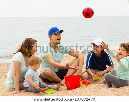 Happy family playing with ball at sandy beach  at summer day - stock photo