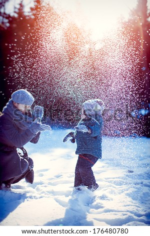 Happy family playing with snow in winter.