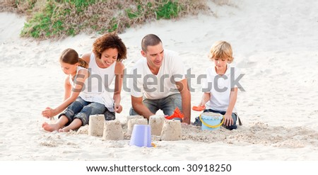 Happy family playing with the sand - stock photo