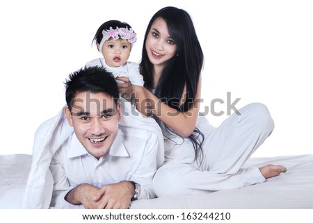 Happy family playing with their baby on the bed isolated over white background - stock photo