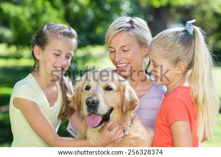 Happy family playing with their dog on a sunny day - stock photo