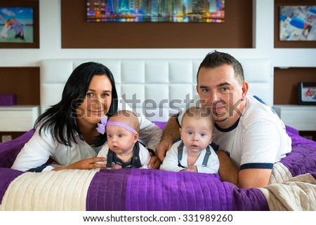 Happy family portrair. Parents with baby boy and girl twins. - stock photo