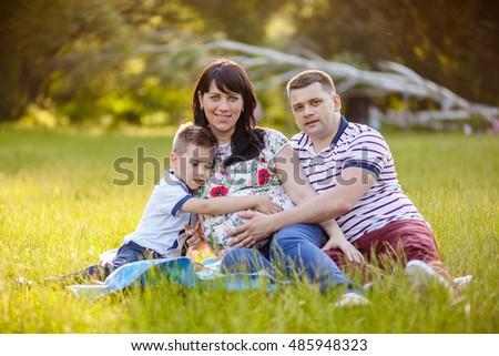 Happy Family portrait Father, pregnant mother and son summer