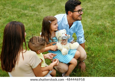 Happy Family Portrait In Nature. Beautiful Smiling Young Parents And Children Spending Time Together In Park. Mother, Daughter, Father And Son  Having Fun Outdoors. Love And Relationships Concept.