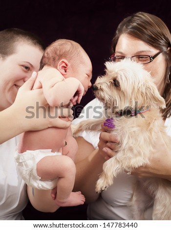 Happy family portrait in the studio. Two mothers, newborn and dog. - stock photo
