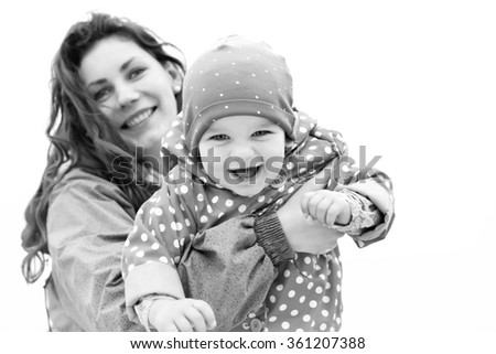 Happy family portrait. Laughing faces, mother holding adorable child baby girl smiling and hugging. Mom and daughter outdoors spring day. Beauty of smile, healthy kid, joyful, expressing love emotions - stock photo