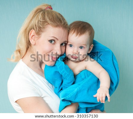 Happy family portrait. Mother with adorable pretty child baby boy, kid covered with bath towel. After shower. - stock photo