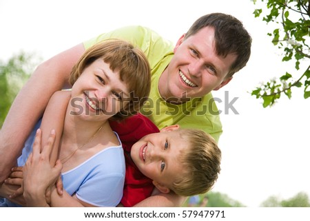 happy family portrait of attractive couple with their young son background on the blue sky - stock photo