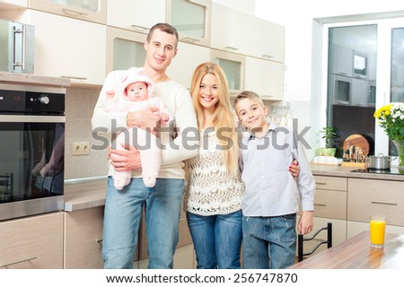 Happy family. Portrait of attractive smiling family standing together in the kitchen. - stock photo