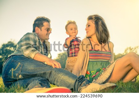 Happy family - Portrait of young beautiful couple with kid having fun in a park - Vintage look - stock photo