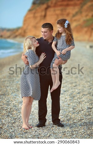 Happy Family Portrait On The Beach Father And Mother Walking With Their Funny Little Daughter