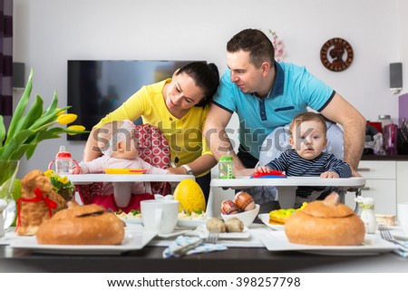 Happy family portrait. Parents with baby boy and girl twins at Easter breakfast - stock photo