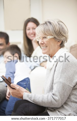 Happy family portrait, senior woman with mobile phone