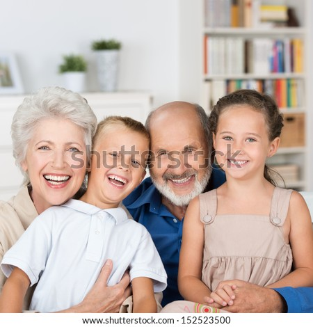 Happy family portrait with a loving elderly couple hugging their laughing young granddaughter and grandson while posing in the living room - stock photo