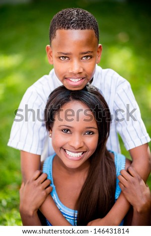Happy family portrait with a son hugging her mother outdoors - stock photo