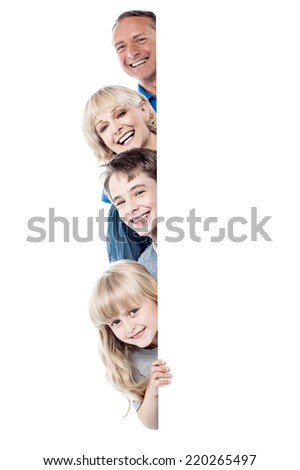 Happy family posing from behind blank whiteboard