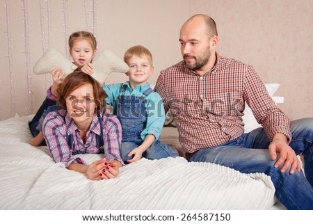 Happy family posing in the studio with Christmas decor - stock photo