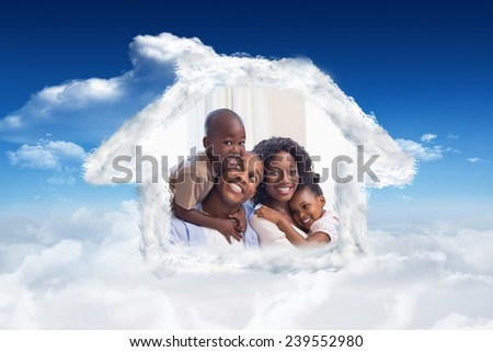 Happy family posing on the couch together against bright blue sky with clouds - stock photo