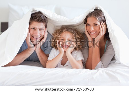 Happy family posing under a duvet while looking at the camera - stock photo