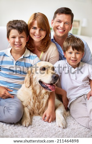 Happy family posing with their dog - stock photo