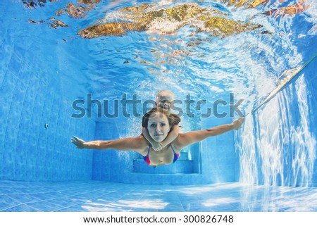 Happy family - positive mother with baby girl swimming and diving underwater with fun in outdoor pool. Healthy lifestyle, active parents, and people water sports activity on summer holidays with child - stock photo