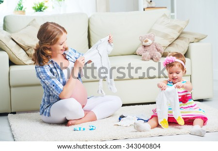 happy family pregnant mother and child daughter preparing clothing for newborn baby - stock photo