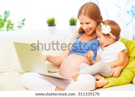Happy family pregnant woman and child  with a laptop on the sofa at home - stock photo
