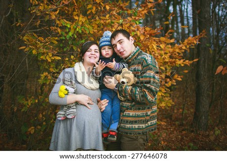 happy family, pregnant woman with her husband and son are walking in the forest - stock photo