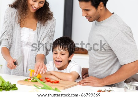 Happy family preparing a salad together in the kitchen at home